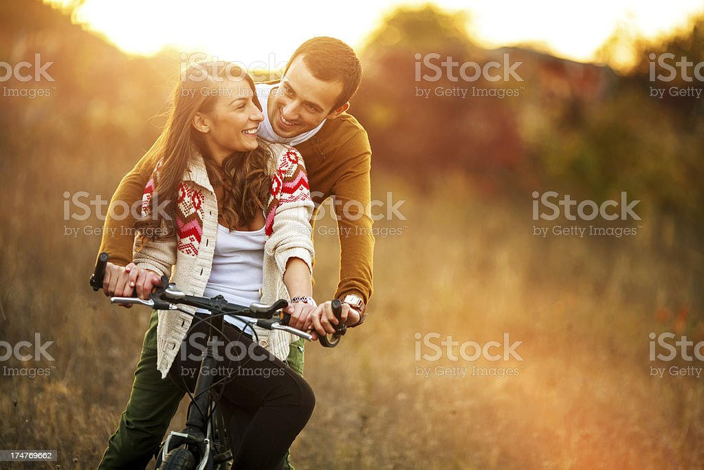 Loving couple driving a bicycle royalty-free stock photo