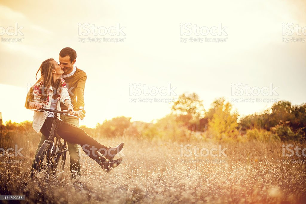 Loving couple driving a bicycle stock photo