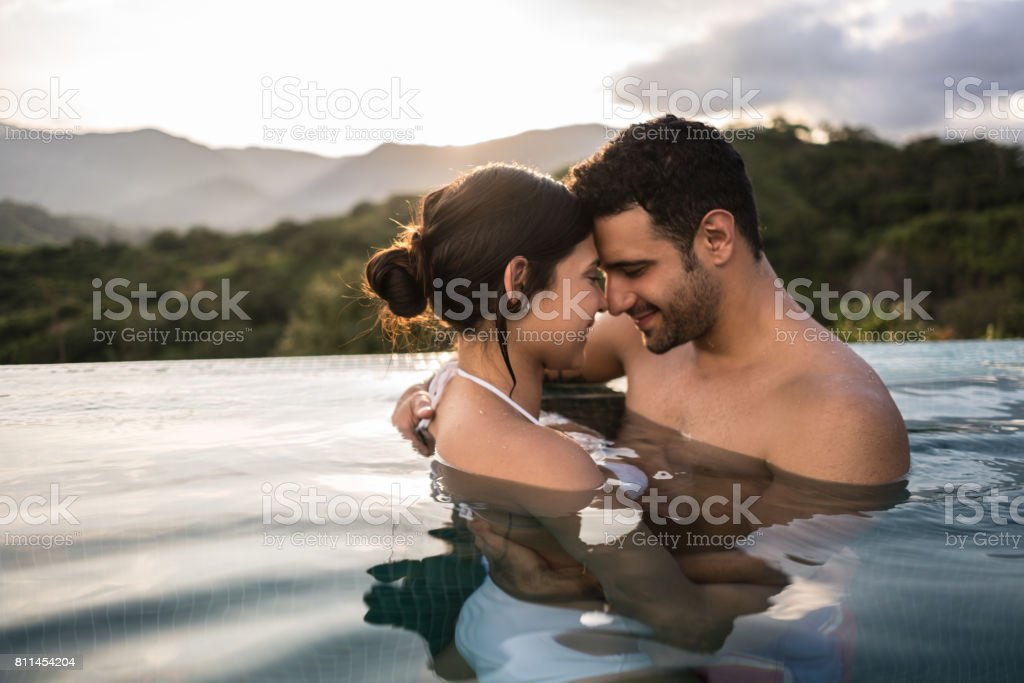 Loving couple enjoying a romantic getaway in the pool stock photo