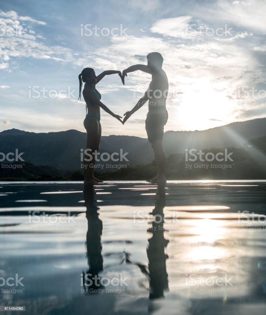 Loving couple enjoying by the pool on a romantic getaway stock photo