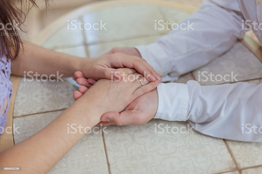 Loving couple holding hands sitting at light table, side view stock photo