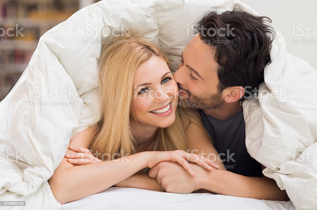Loving couple in bed stock photo