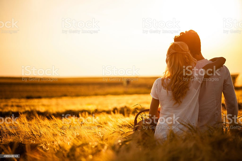Loving couple in wheat field stock photo