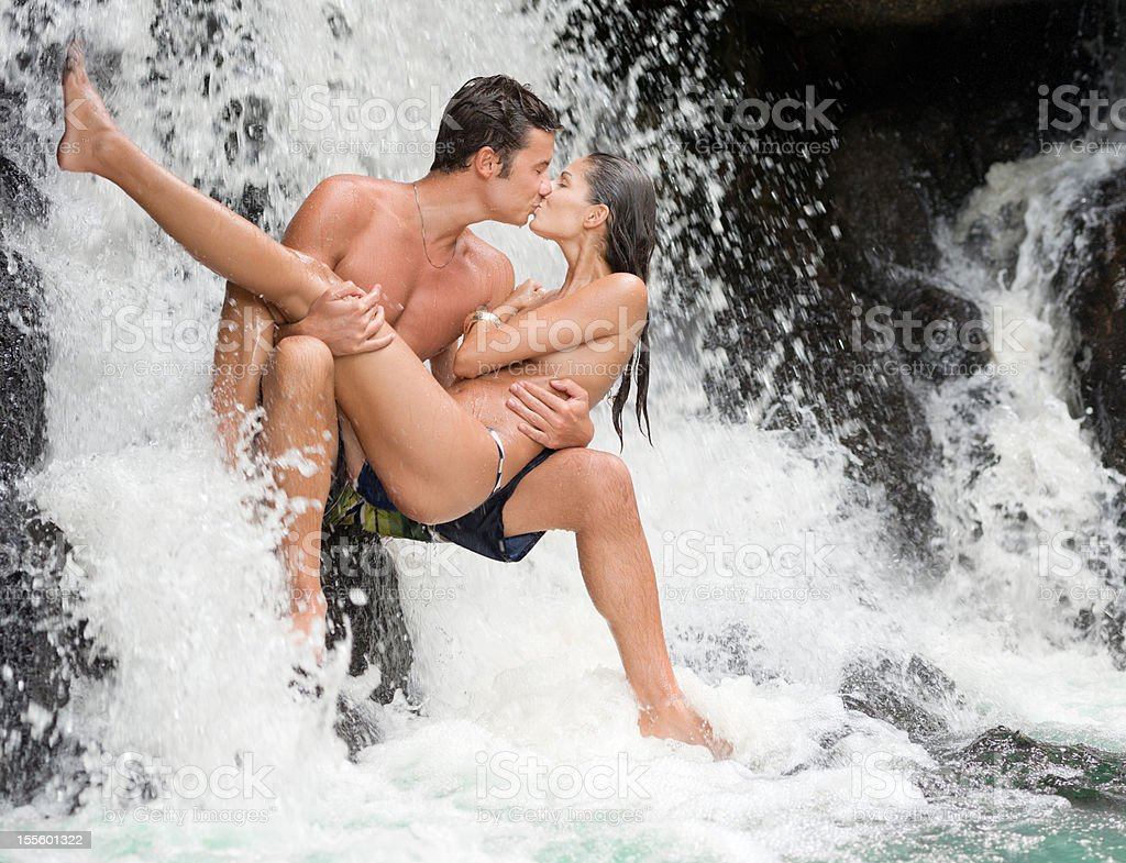 Loving Couple kissing under a Waterfall (XXXL) royalty-free stock photo