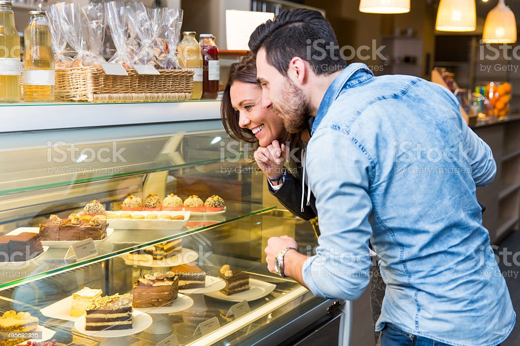 Loving couple looking at display window with cakes stock photo