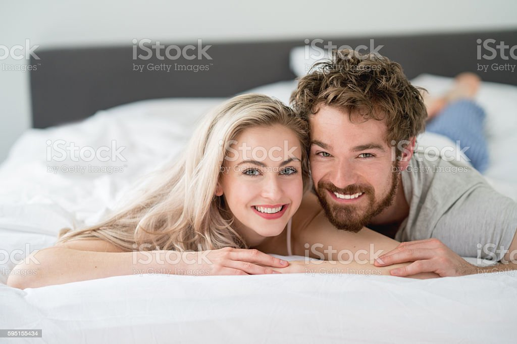 Loving couple lying in bed stock photo