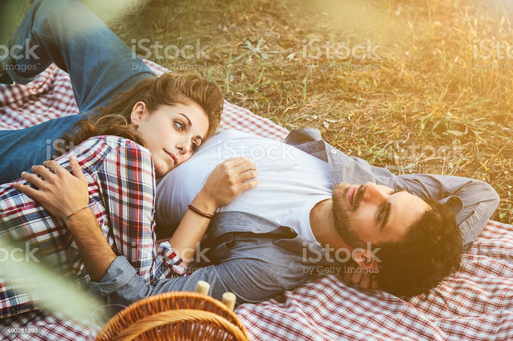 Loving couple lying on the grass stock photo