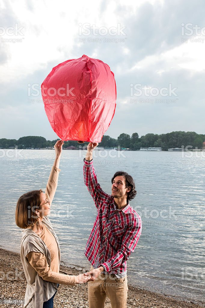 Loving couple on beach releasing Chinese lampion in the air. stock photo