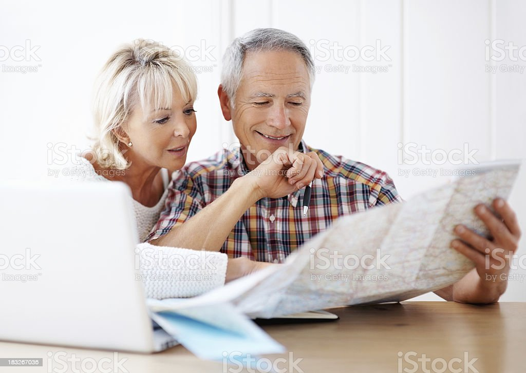 Loving couple planning vacation with map and laptop stock photo