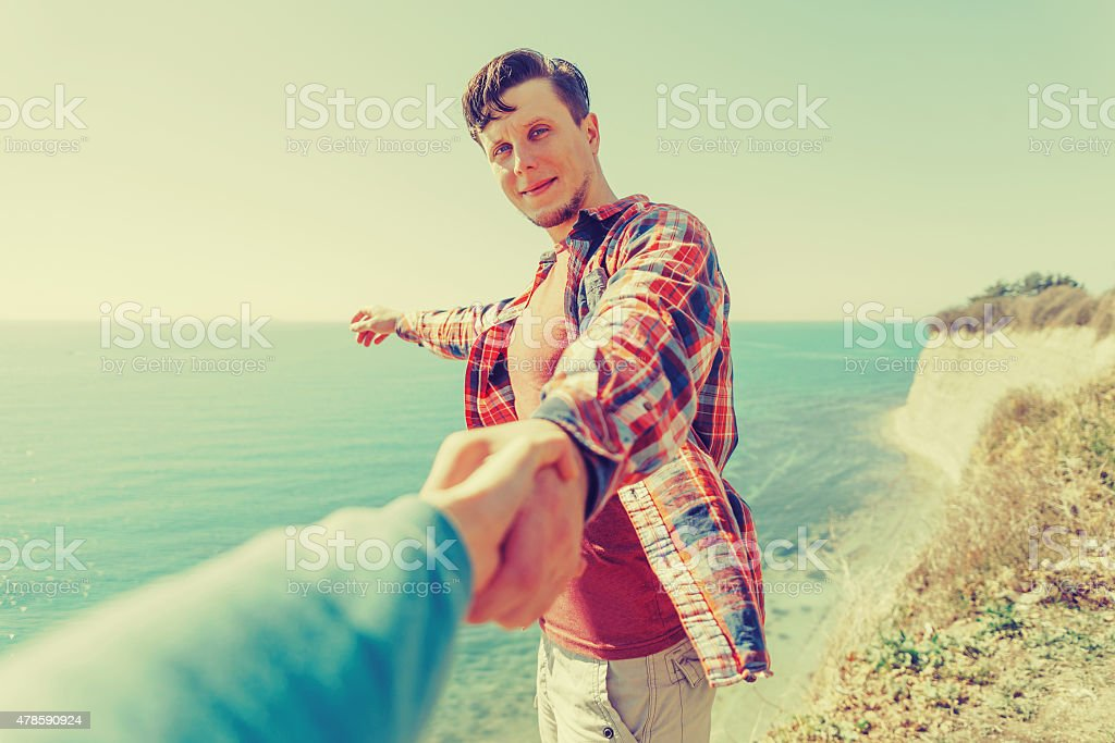 Loving couple resting on coastline near the sea in summer stock photo