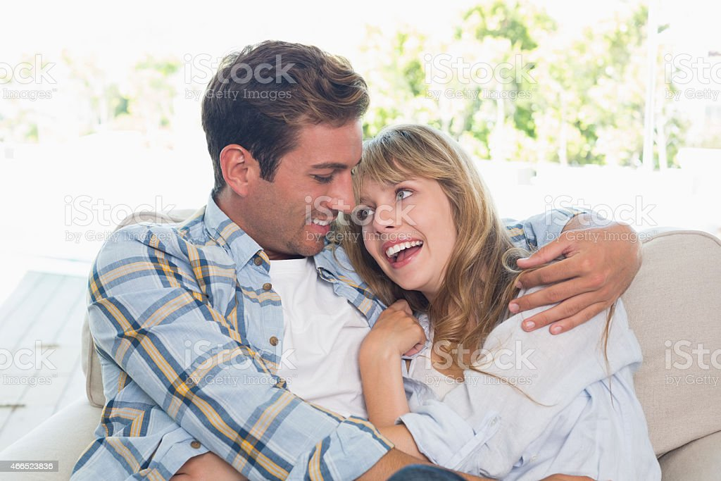 Loving couple sitting on couch at home stock photo