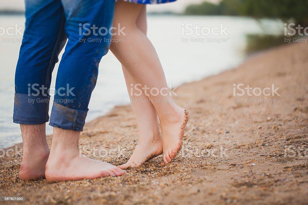 Loving couple sitting on the beach, feet close-up stock photo