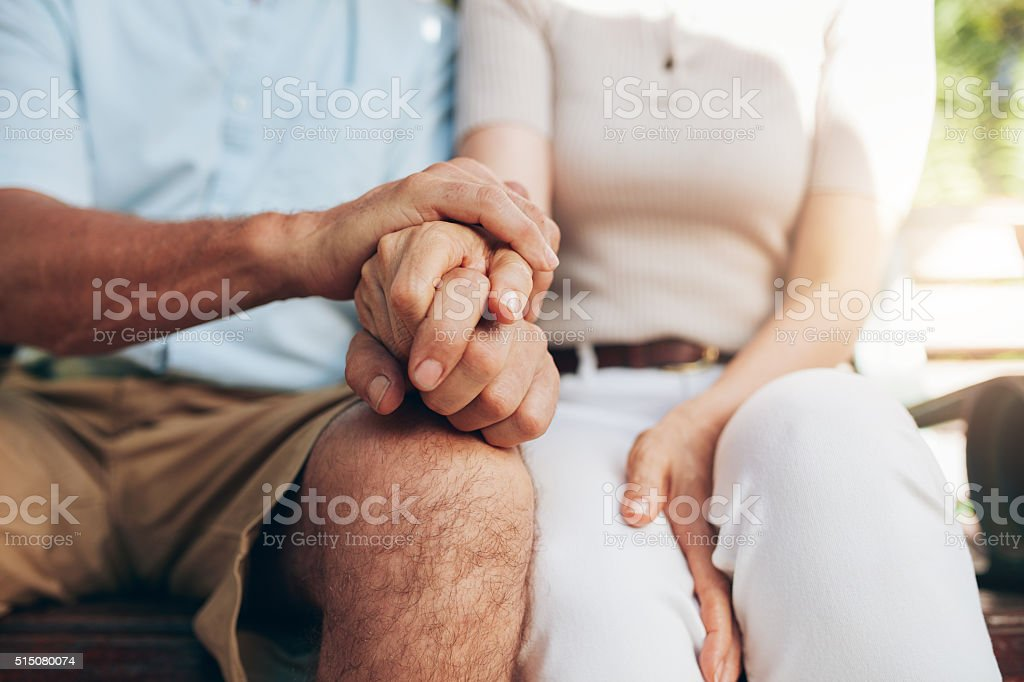 Loving couple sitting together and holding hands stock photo