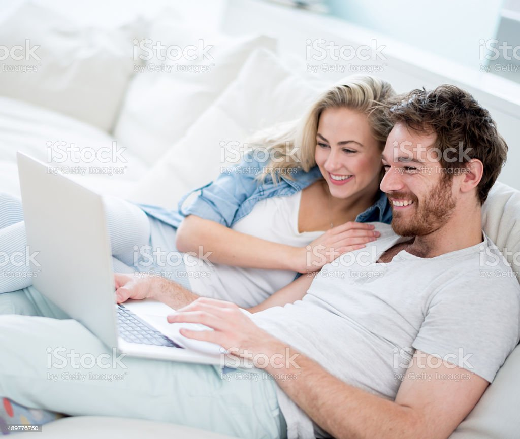 Loving couple social networking on a laptop at home stock photo