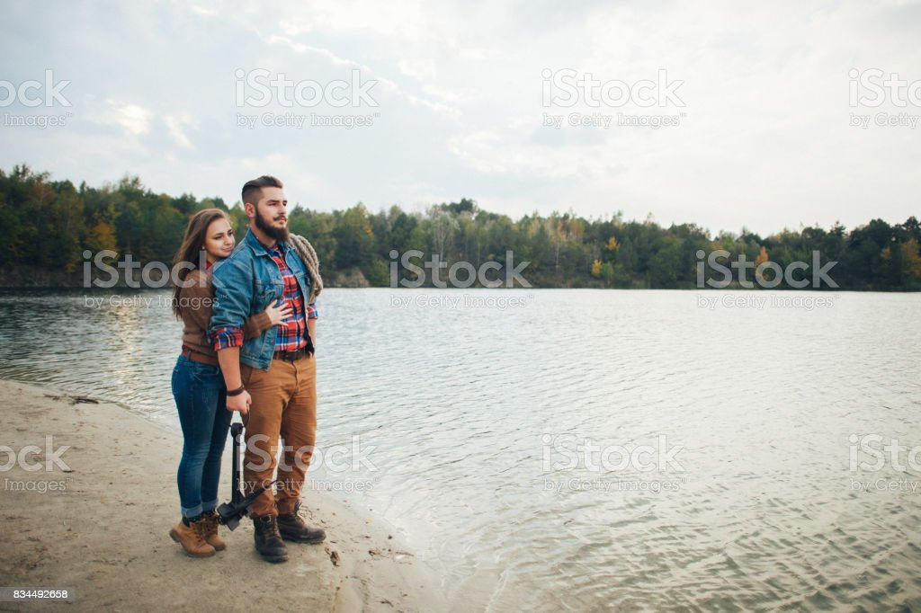 A loving couple stand on the bank of a mountain river, embracing each other stock photo