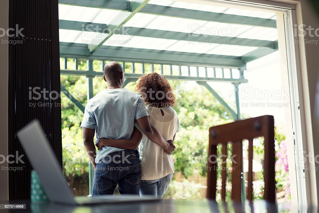 Loving couple standing with arms around at home stock photo