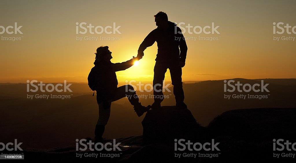 Loving couple walking holding hands Silhouetted by the sunset royalty-free stock photo