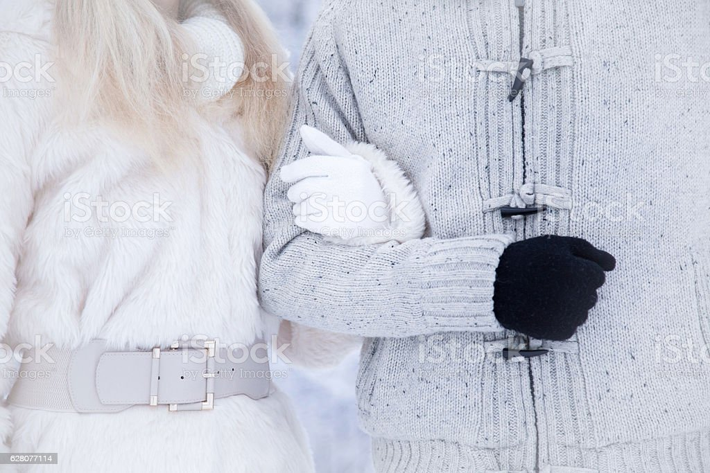 Loving couple wearing warm clothes and walking in winter day. stock photo