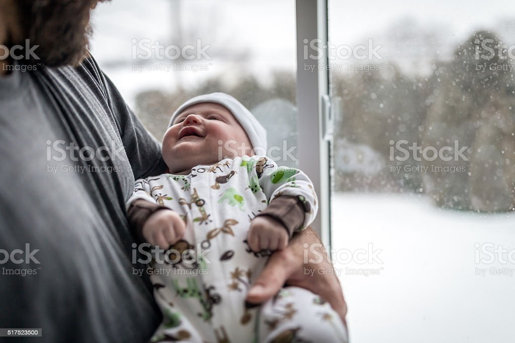 Loving Dad With Newborn Baby Close to Window in Winter stock photo