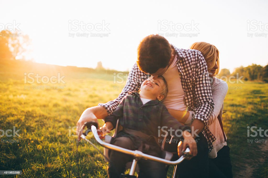 Loving family on a bicycle stock photo