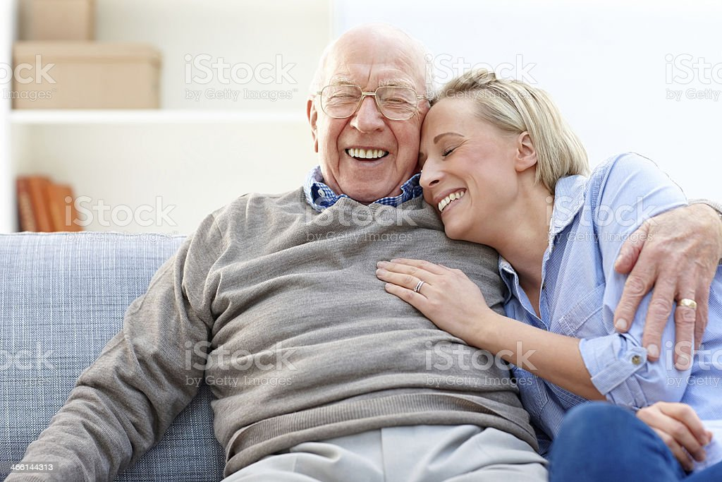 Loving father and daughter together on sofa stock photo