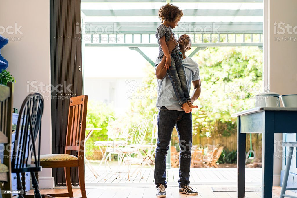 Loving father lifting girl at home stock photo