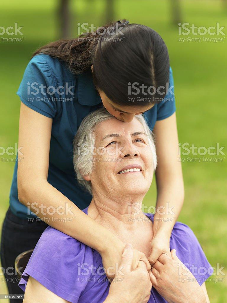 Loving grandchild kissing her grandmother royalty-free stock photo