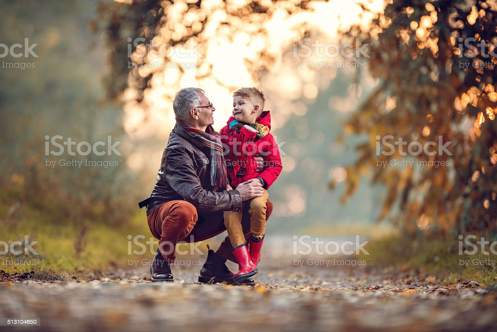 Loving grandfather and grandson talking to each other in autumn. stock photo