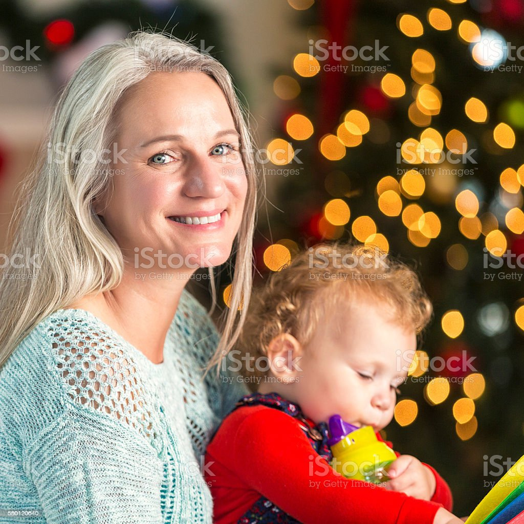 Loving grandmother holds baby granddaughter on Christmas Eve stock photo
