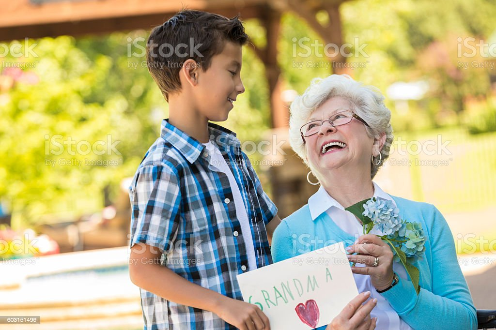 Loving grandmother looks up at her grandson stock photo