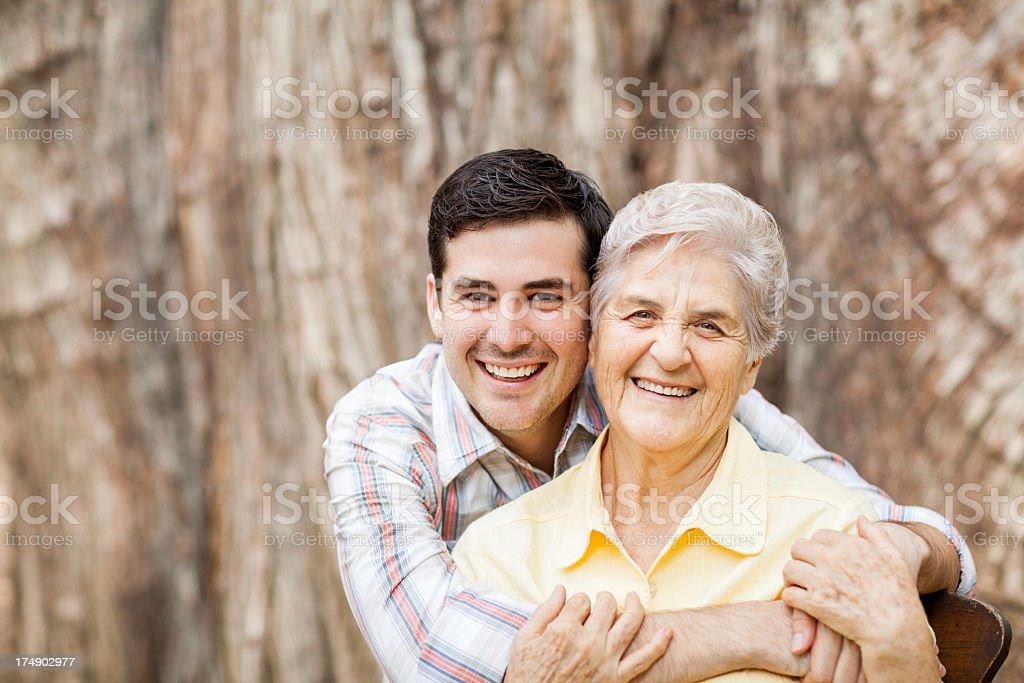 Loving grandson hugging his grandmother royalty-free stock photo