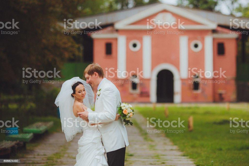 Любящий жених обнимает свою невесту. Свадебная церемония stock photo