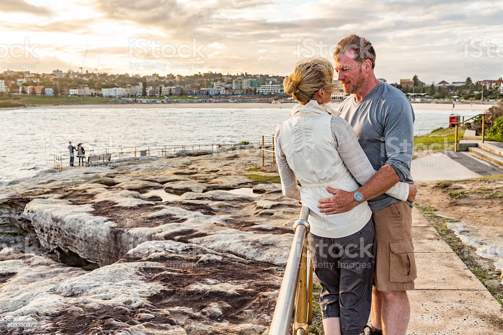 Loving Happy Middle Aged Fit Healthy Beach Couple at Sunset stock photo