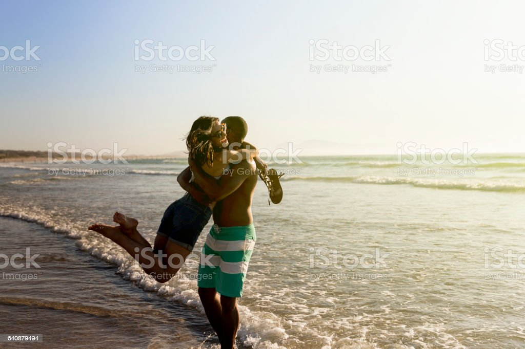Loving man carrying woman on shore at beach stock photo