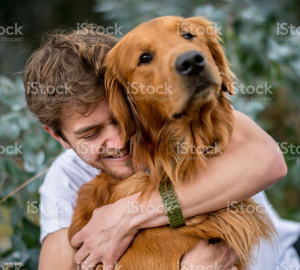 Loving man hugging his dog stock photo