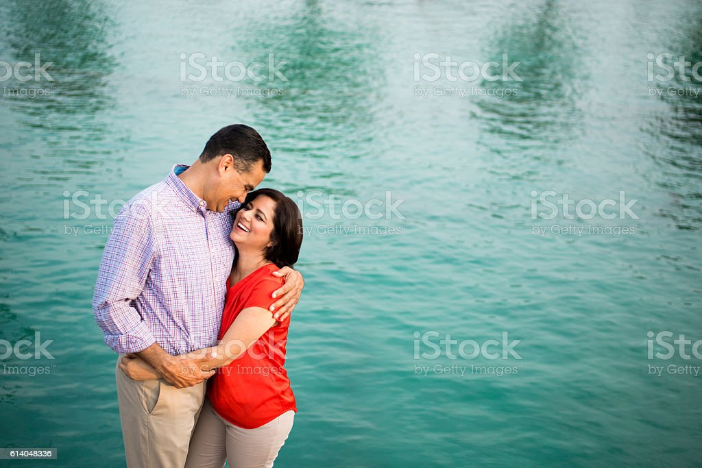 Loving mature couple embracing and smiling face to face stock photo