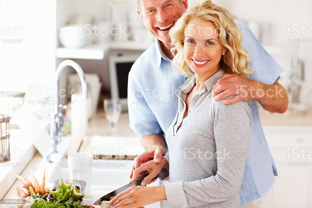 Loving mature couple preparing food together in the kitchen stock photo