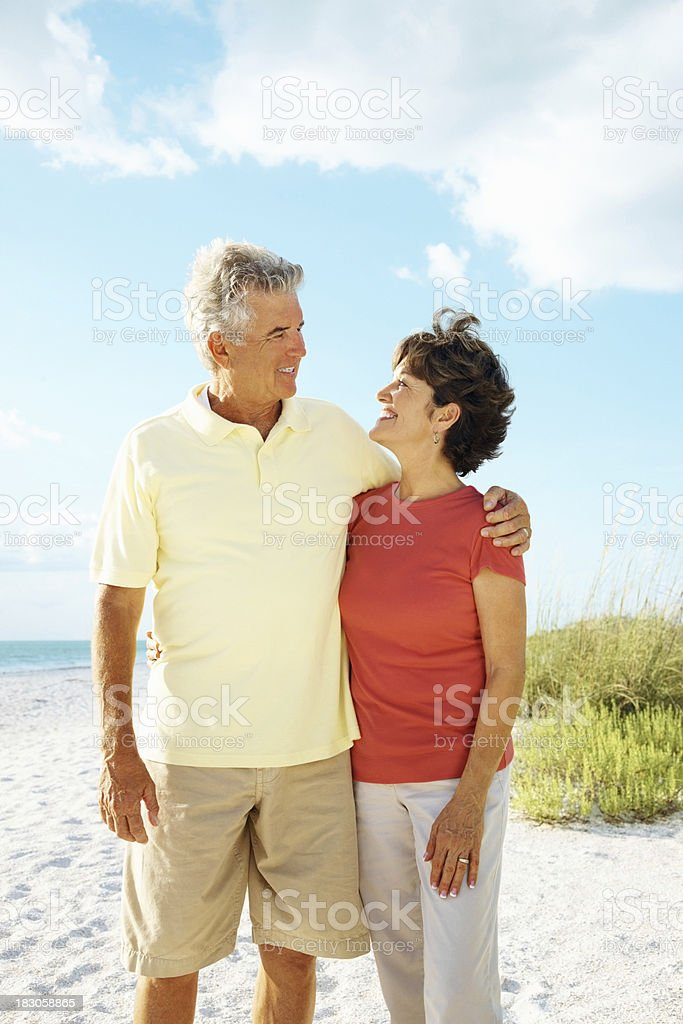 Loving mature couple with arms around standing on a beach royalty-free stock photo