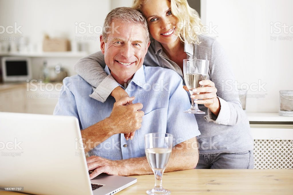 Loving mature couple with wineglasses and laptop in kitchen royalty-free stock photo