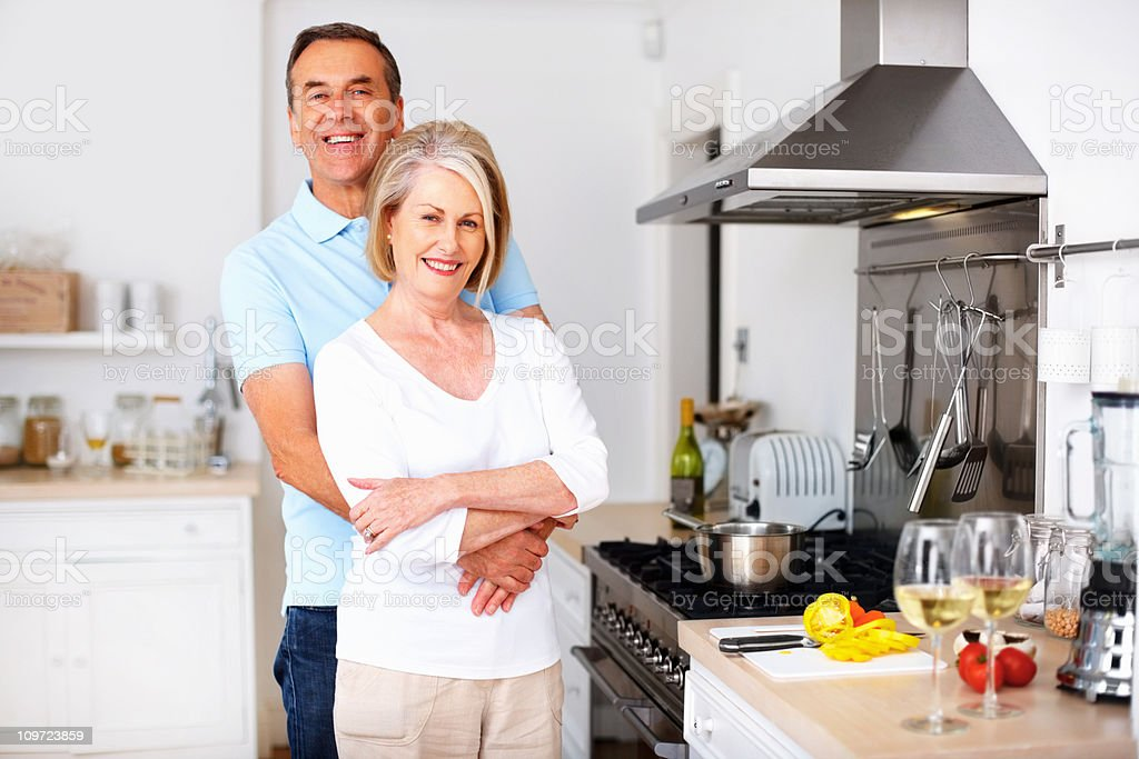 Loving mature man embracing wife from behind at kitchen royalty-free stock photo
