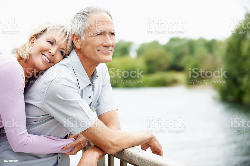 Loving mature woman embracing a man from back royalty-free stock photo