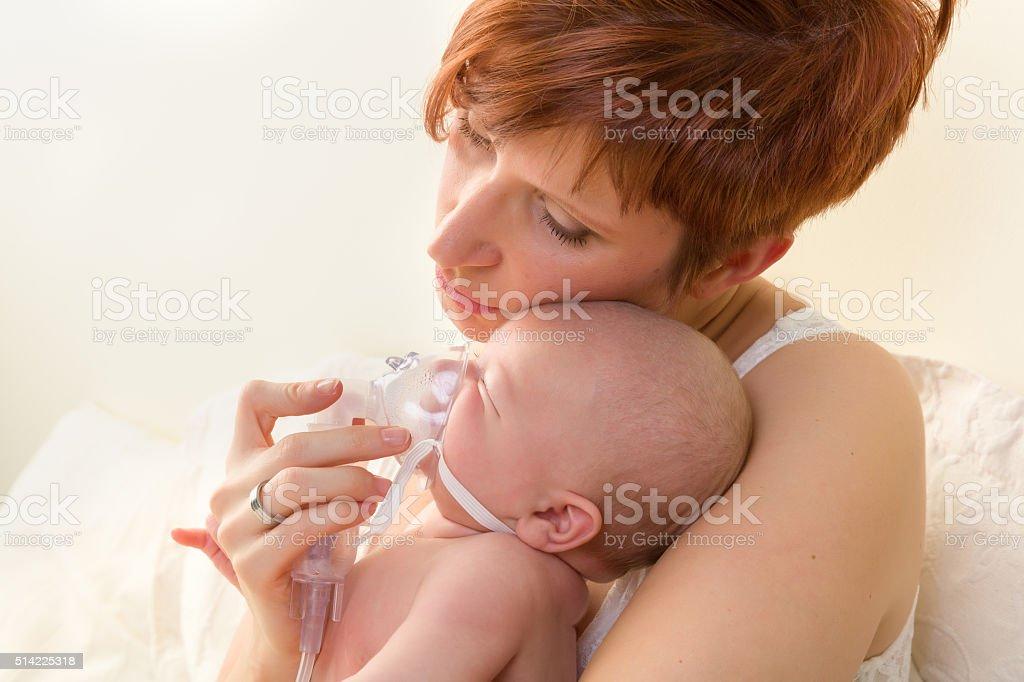 Loving mom treating sick baby stock photo