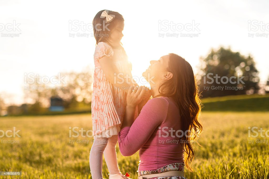 Loving mother and daughter communicating during spring day at sunset. stock photo