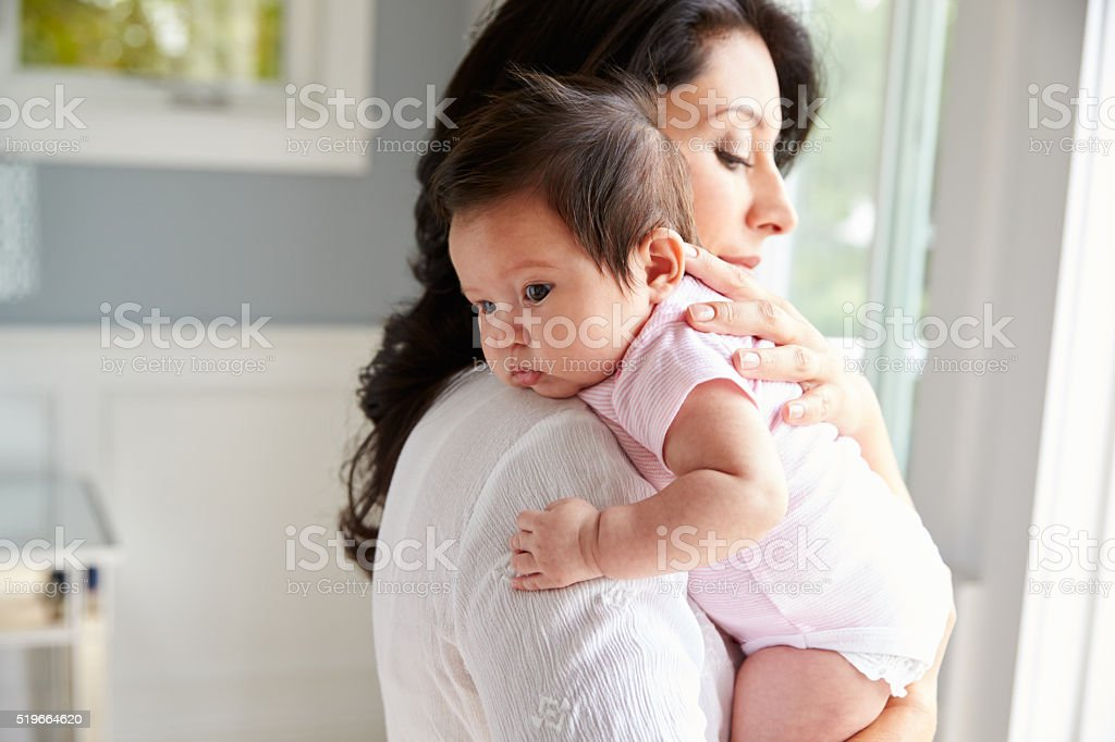 Loving Mother Holding Baby Daughter At Home stock photo