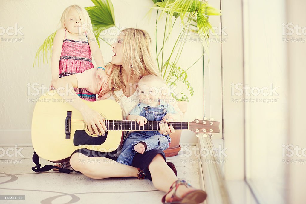 loving mother infant son little girl indoors stock photo