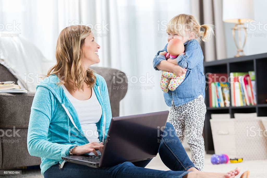 Loving mother smiles at daughter while using laptop stock photo