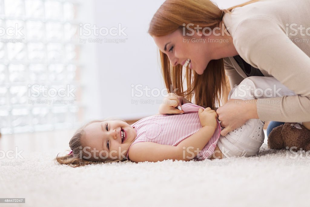 Loving mother tickling her little girl on carpet at home stock photo
