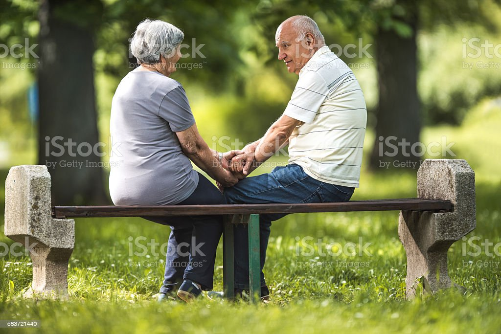 Loving old couple communicating on a bench in the park. stock photo