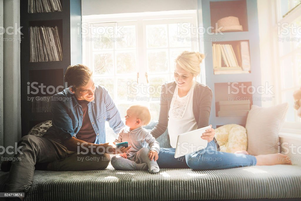 Loving parents showing technologies to baby at home stock photo