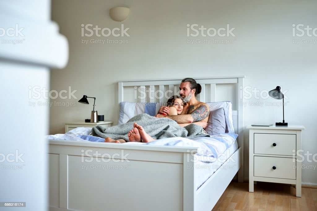 Loving pregnant couple in bed at home stock photo